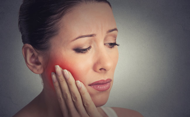 Woman demonstrating tooth pain.